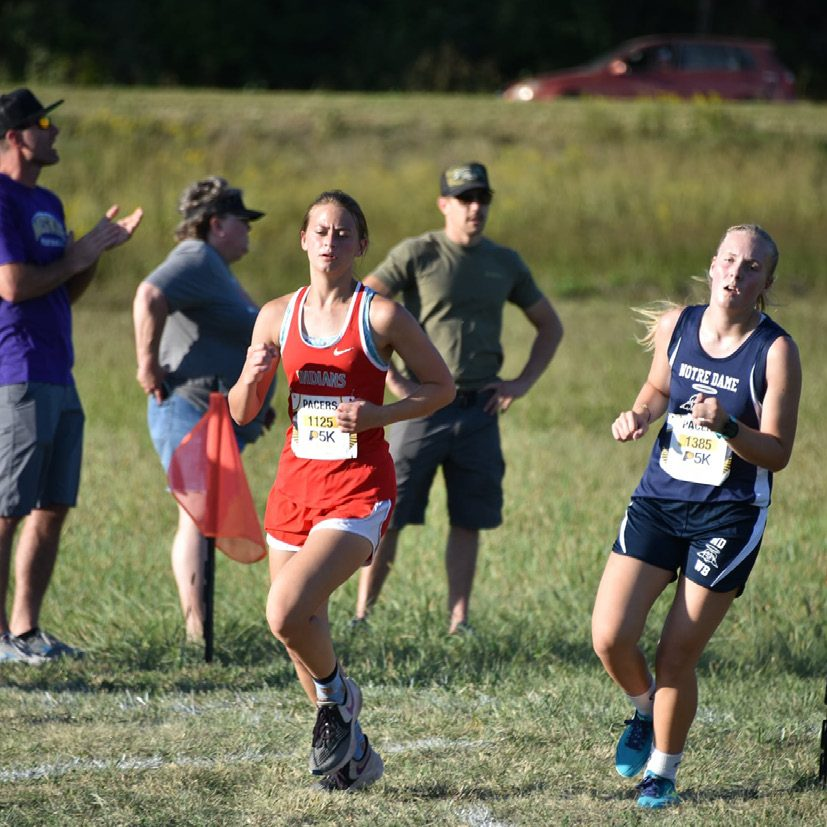 Delana Hess battles a Notre Dame runner at the Ft. Madison Invitational. Photo by Angela Buschling.